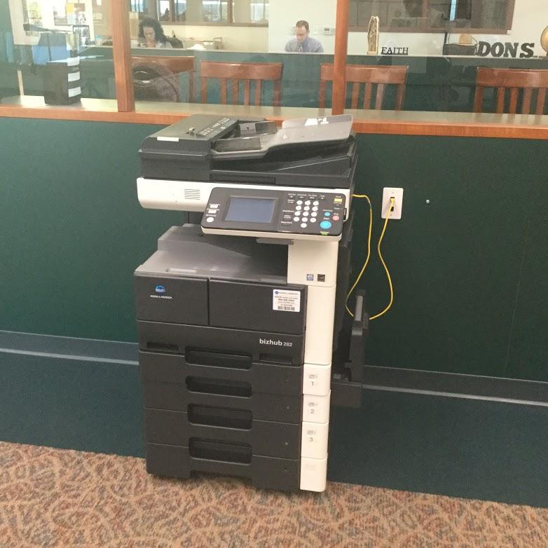 The printer is located in the front corner of the library behind the flag.