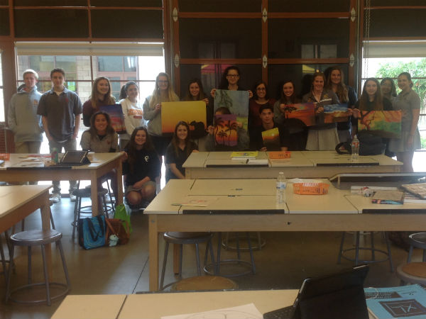 Ms. Goyette's art class poses with some of their works of art