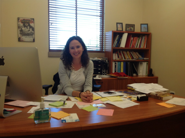 Mrs. Conroy sits at her desk in the Attendenace Office