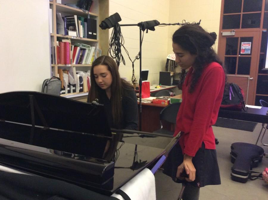 Rachel Wilson plays piano with Niki Maroon accompanying her on vocals while practicing in the Schola classroom.