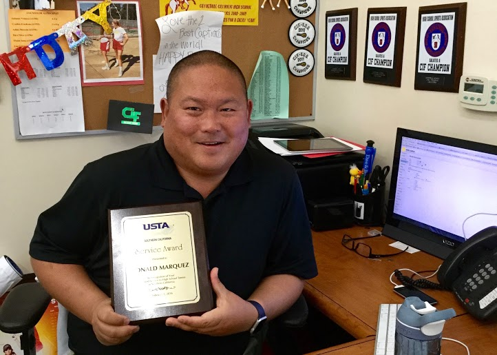 Mr.+Ron+Marquez+proudly+displays+his+award+from+the+United+States+Tennis+Association+in+his+office+at+CCHS.+
