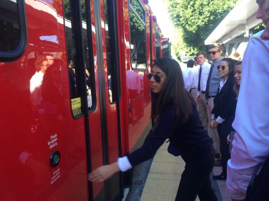 Eliza Lozano '16 opens the trolley door for her classmates at the Morena- Linda Vista trolley station in San Diego. Students from Cathedral Catholic's American government classes took a fieldtrip to the Superior Court of California, San Diego on Wednesday.