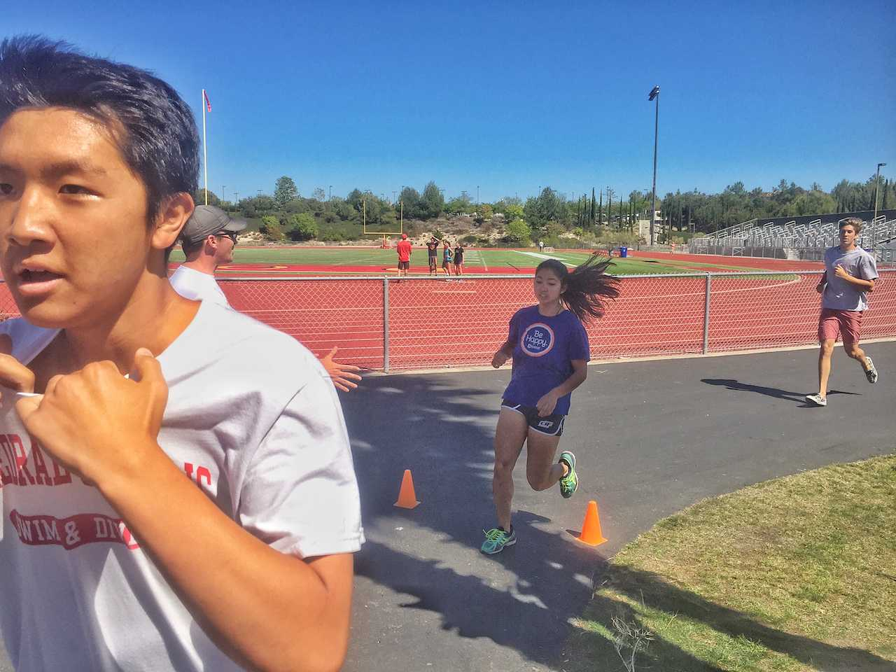 Young Han '18 prepares to dive into the swimming portion of the swim and track meet while Claire Hobrock '16 crosses the finish line to the running portion and Dennis Blyashov '17 trails behind.