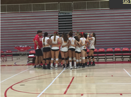 The varsity girls volleyball team huddles up in preparation for their first game of the season