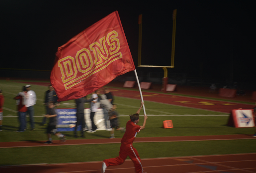 Varsity cheerleader Chris Lucio '18 runs the Cathedral Catholic High School flag down the stretch of the track as the Dons' football team scores a touchdown against Mira Mesa High School.