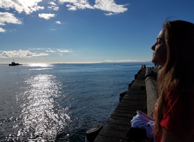 Varsity water polo player Laura Larkin '18 sits on the pier of Stearn's Wharf in Santa Barbara as she gazes out into the sea planning her next game at the Tournament Of Champions.