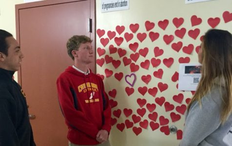 CCHS students JP Sperrazzo '17, Michael Robinson '17, and Delara Bahadoori '18 ponder the deeper meaning behind the hearts that wrap around the De Sales building. The hearts, which are posted by Ms. Christine LaPorte's classes, represent aborted children in the U.S.