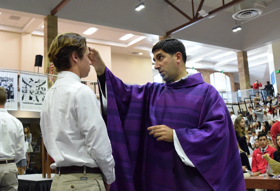 Father Martin Latiff spreads ashes in the sign of the cross on Nick Mahmood's '17 forehead. CCHS participated in the Ash Wednesday mass to open the season of Lent, a time for sacrifice.