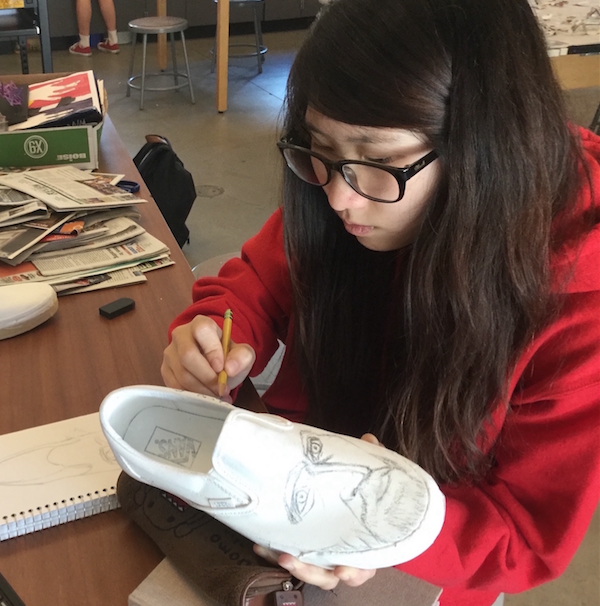 CCHS artist Jenny Park '18 sketches on a white canvas Vans shoe for the Art Club, which is participating in the Vans shoe design contest where a school can design and paint shoes for a monetary award and an art school scholarship.
