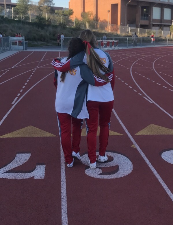 Amanda Williams '17 savors her last months as a senior and athlete during a track and field meet, walking with arms around Kiki Carney '18 as they cherish the warm weather after a long day of running.