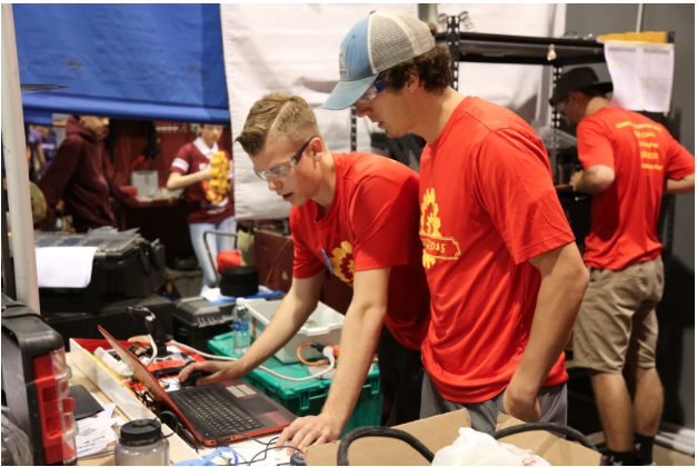 CCHS robotics leader Andrew Knoll advises Tommy Twomey '18 while he makes last minute changes to the school's competitive robot Big Redd.
