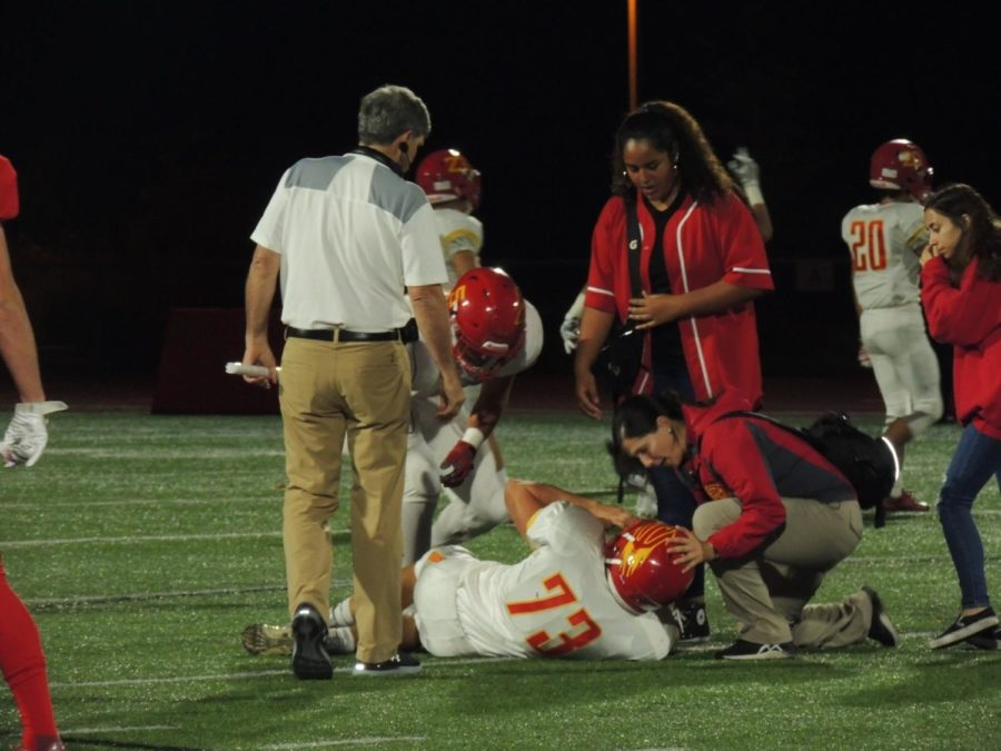 Coach Sean Doyle exemplifies good sportsmanship as he checks up on an injured Mount Carmel player during last Fridays game.