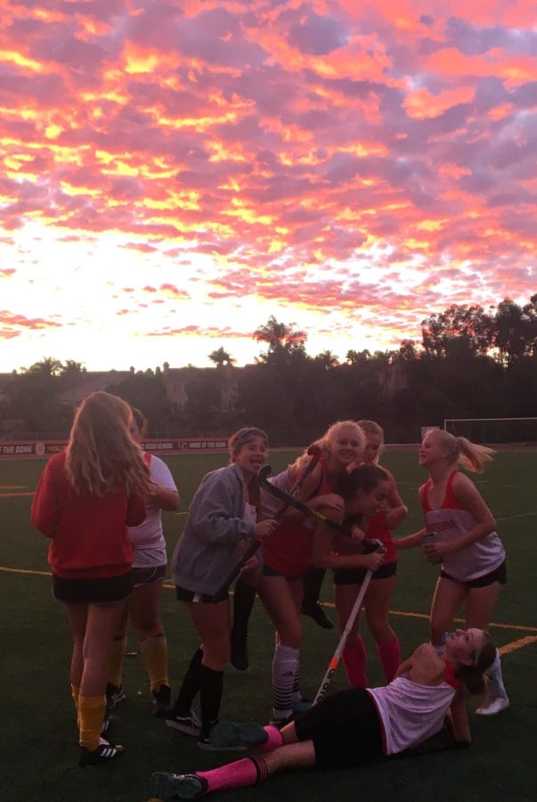 The junior varsity field hockey team celebrates the end of its season by taking photos with the sunset after its last practice on Wednesday afternoon.