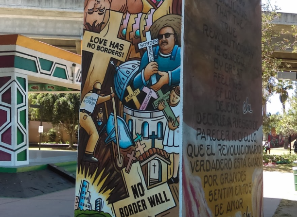 """Controversial mural in Chicano Park painted by Salvador Barajas expresses the pain of Mexican-Americans by displaying an ICE official strangling a Mexican worker who is handing money to a woman in tears, illustrating crosses with expressions like """"Love has no Borders"""" and """"No Border Wall""""."""
