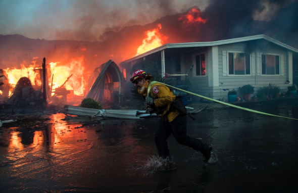 A fireman from the Oceanside Fire Department bravely rushes to the scene of the Lilac Fire, hose in hand, in an attempt to save the surrounding houses from damage.
