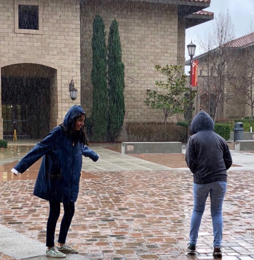 Linna Luna Bravo '18 and Laila Emamjomeh '20, the only two students in sight, enjoy the rainy weather in the Academic Quad on Tuesday, despite being drenched from head-to-toe.