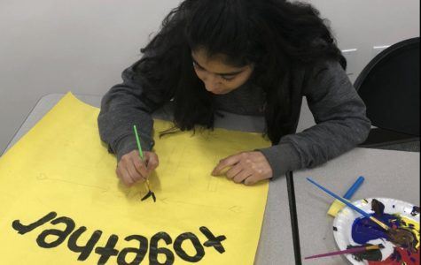 Linna Luna Bravo '18, along with other members of CCHS's Peers Living United in Solidarity (PLUS) club, paints a poster sporting the phrase