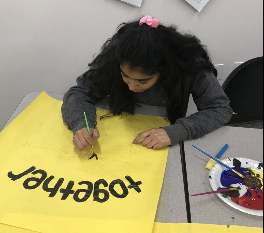 Linna Luna Bravo 18, along with other members of CCHSs Peers Living United in Solidarity (PLUS) club, paints a poster sporting the phrase together we rise after school on Thursday in preparation for the Womens March on Saturday.