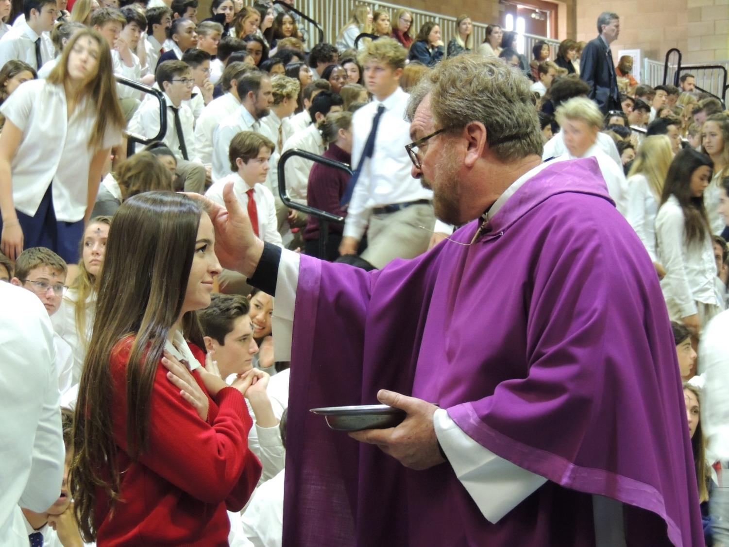 Fr. Michael White anoints a CCHS student with ashes during Ash Wednesday Mass.