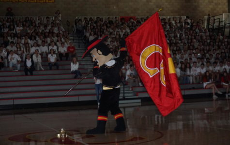 The Don, the CCHS mascot, anticipates  setting the CCHS flag in a flag stand as CCHS students watch intently at the Spring Sports Rally Friday.