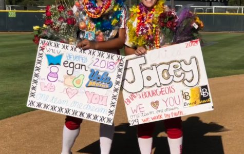 CCHS varsity softball players Megan Faraimo '18 and Jacey Bourgeois '18 sport the leis, flowers, and posters given to them on senior night Wednesday after the team beat University City High School 11-0.