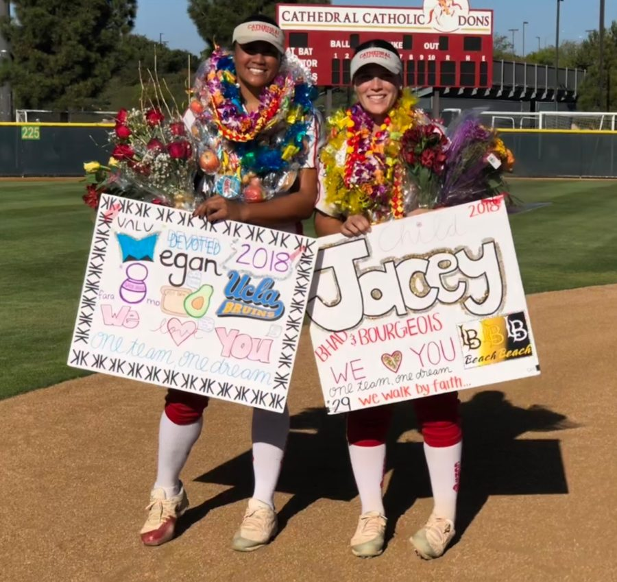 CCHS varsity softball players Megan Faraimo 18 and Jacey Bourgeois 18 sport the leis, flowers, and posters given to them on senior night Wednesday after the team beat University City High School 11-0.