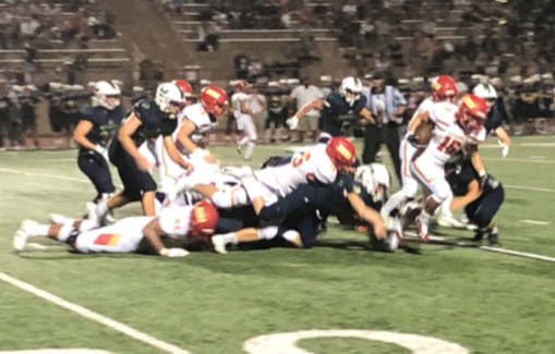 Running back Shawn Poma '19 breaks away from tacklers for a large gain in the fourth quarter of last Friday's season opener at La Costa Canyon High School.