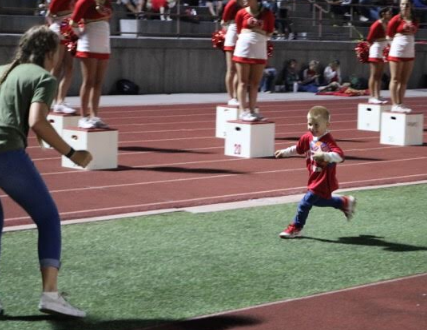 CCHS football games prove to be fun for the whole family, as Sophia Manos '21 participates in her own football game with a young future Don.