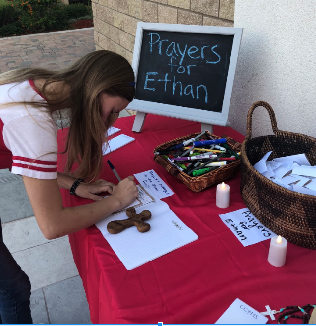 Kate Foster '20 writes a special prayer for Ethan Olson and his family at the prayer table Friday morning outside the St. Therese Chapel. During lunch, the CCHS community held a mass dedicated to the Olson family.