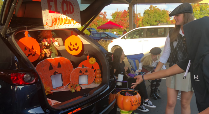 Delaney Fritz '20, a CCHS National Honor Society member, watches as a young attendee tosses a plastic pumpkin at the El Cid trunk at the Trunk or Treat event Thursday.