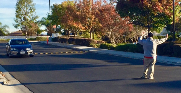 Cathedral Catholic High School security guard Mr. Jason Gigliotti oversees student traffic in the student parking in order to make sure student drivers pay attention to the road around pedestrians and other parent drivers.