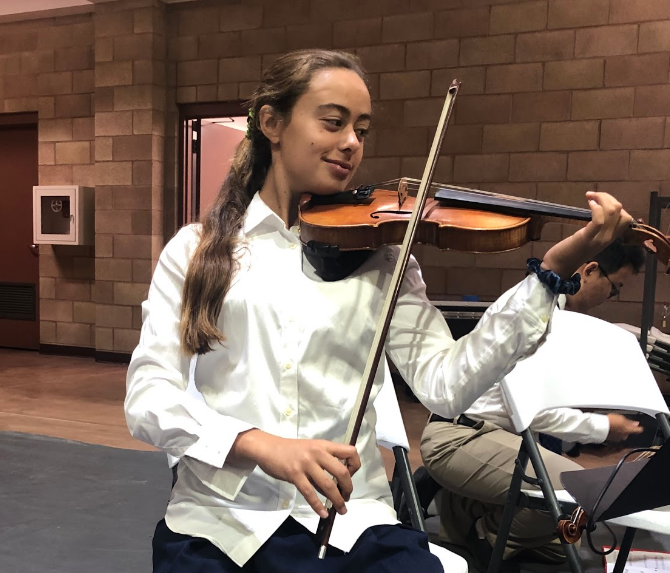 Natasha Tavares '22 warms up on her violin before the All Saints Day mass Thursday in the Claver Center. The mass included a special procession by Mr. Brian Frice's red three Campus Ministry 11 class, who carried in posters depicting various saints.