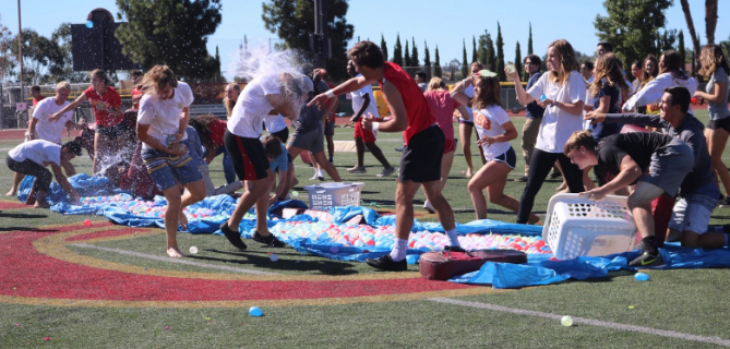 Jake Rons '19 smashes a water balloon on opponent Andre Duisters '19 during Friday's senior water balloon fight. The class of 2019 gathered on the football field during lunch to battle against peers and add some fun to a stressful time.