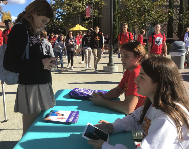 Morgan Yacullo '20 (left) signs up for Best Buddies, a nonprofit organization dedicated to creating opportunities for one-to-one friendships for children and teenagers with disabilities, during lunch Friday at a booth run by options mentors Alicia Morales '19 (right) and Holden Brosnan '20 (middle).