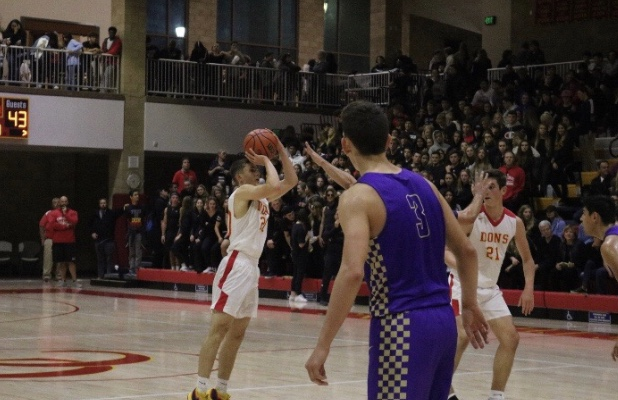 Dons+guard+Alex+Wade+%E2%80%9821+pulls+up+from+the+three-point-line+during+the+third+quarter+in+the+Holy+War+between+Cathedral+Catholic+High+School+and+Saint+Augustine+High+School.+