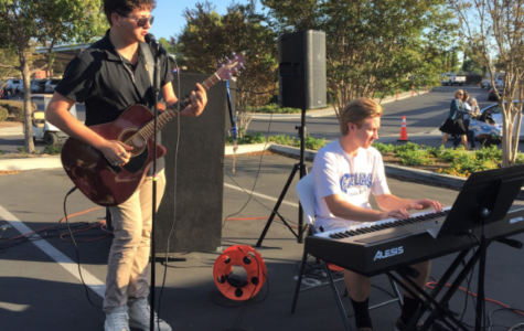 During the annual Trunk or Treat event at Cathedral Catholic High School, Sergio Vinas '20, left, and Philip Krol '19, right, entertain the middle and elementary school children and their guardians with music as they take part in Halloween activities.