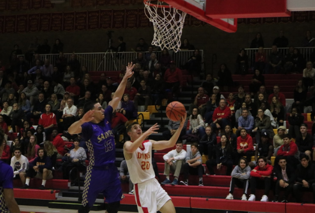 CCHS player Alex Wade '21  attempts a layup on SAHS player Misa Rosado '19  last Thursday in the Claver Center. Wade attempted to lead the Dons back to the top, but the team fell short 62-55 to the Saintsmen. Many fans attribute the loss to the excessive drives toward the hoop rather than taking outside shots, while other people say the result was due to turnovers.