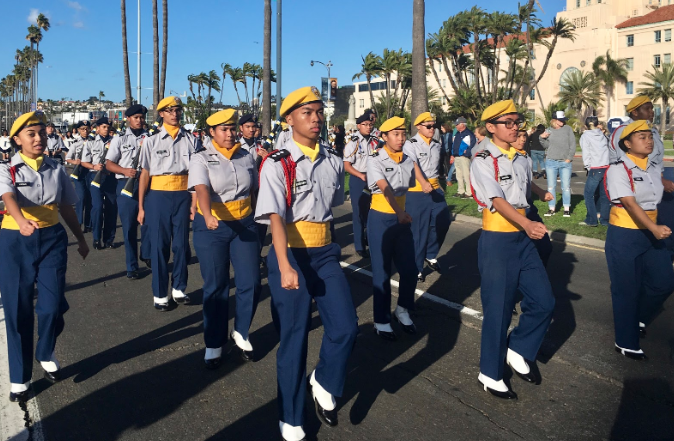 The Morse High School band and drill team march down Harbor Drive while the audience cheers from the sidelines.
