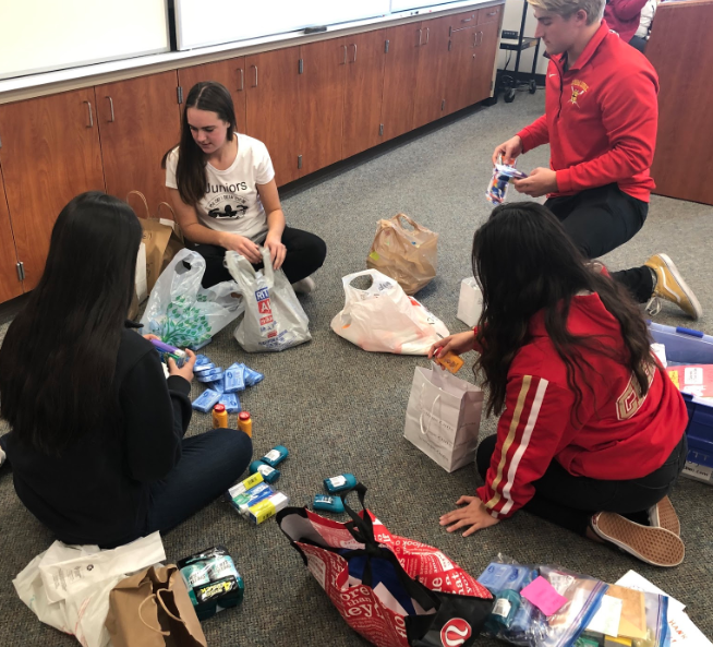 Remy Reeb '20, Delayne Fritz '20, Lisette Gomez-Galvan '20, and Sean Vandegrift '19 (left to right) organize toiletry donations for the NHS project called On the Go, an effort to create toiletry bags for nearby firefighters, who are required to keep the bags stocked with three days worth of personal items at all times in order to respond to calls as quickly as possible.
