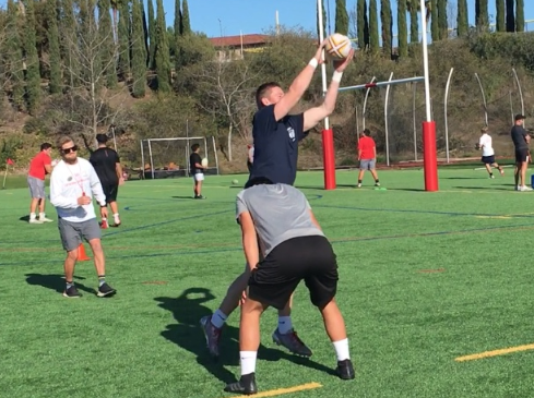 As coach Charles Purdon (left) looks on, teammates Miles McCormick '19 and Levi Summerlin '19 practice a line out, a move done to restart the ball from an out of bounds position, to prepare for their game against St. John Bosco on Saturday. The varsity boys rugby team lost the game 42-29, breaking its winning streak, but the team looks to win next Saturday against St. Augustine High School.