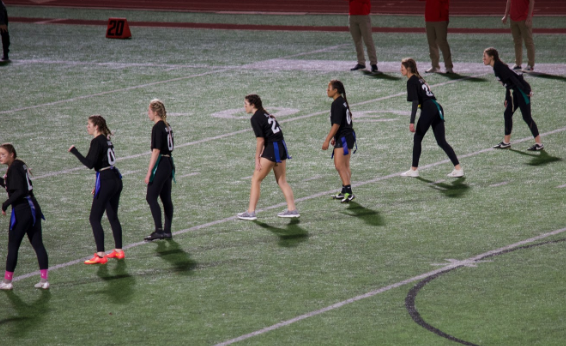 Dressed in matching black jerseys and braids, the senior team lines up on the field at halftime during Saturday night's annual senior versus junior powderpuff game. Coached by members of the boys varsity football team, the senior team dominated the game, winning 27-0.