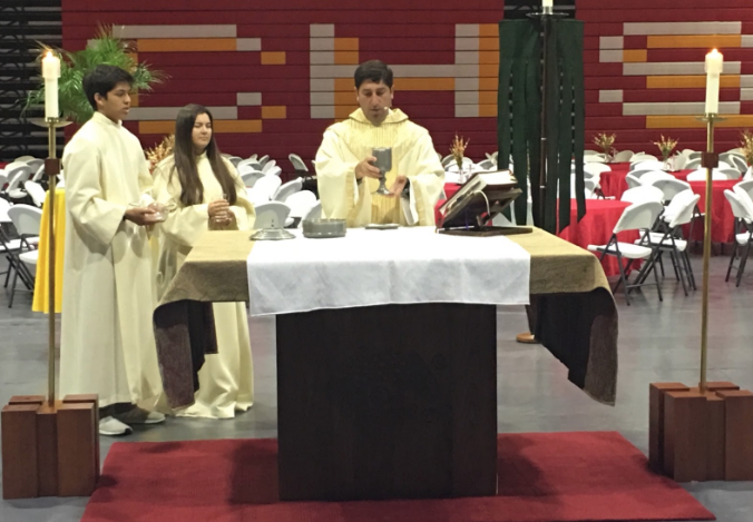 Father Martin Latiff (right), holding up the chalice during the Junior Unity Mass, blesses the wine with assistance from altar servers Carson Duenas '20 (left) and Jocy Rogers '20 (middle) Monday in the Claver Center.