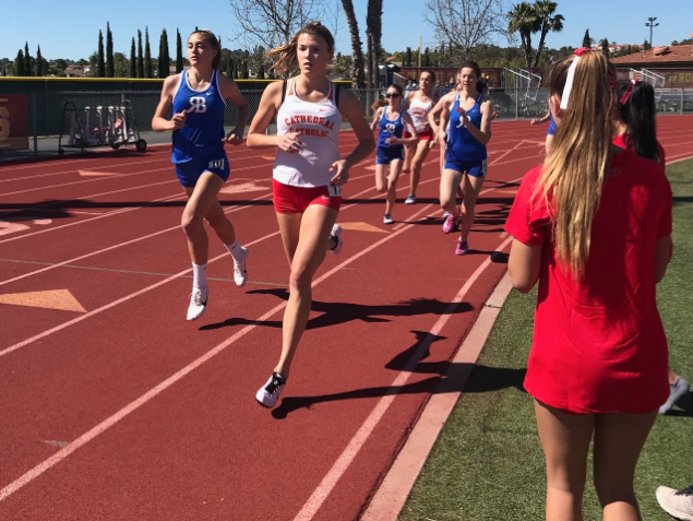 Liz Houk '20 rounds the first curve of the varsity 800-meter event, cheered on by fellow members of the track and field team in Saturday's meet against Rancho Bernardo High School.