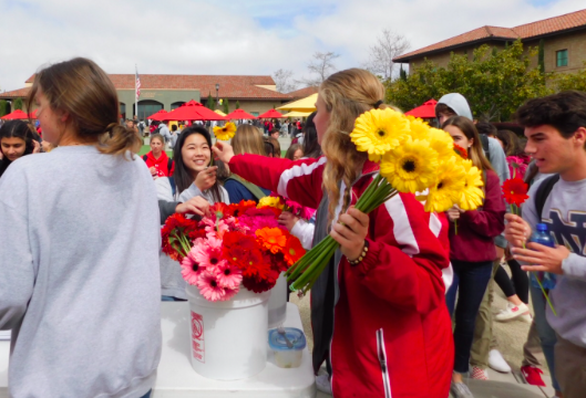 CCHS student Hailey Colman '19 passes a flower to Olivia Sung '19 as a part of Life Week's Celebrate Life Friday, a day that hopes to inspire happiness around campus and celebrate all life.