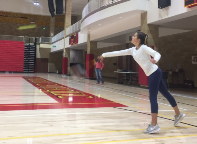 Ali Viana '20 practices a serve in the Claver Center during the last day of badminton tryouts in hopes of making the varsity team.