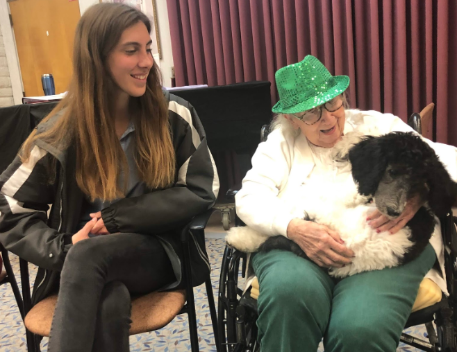 Julia Van Wey (left) gazes at Mrs. Carol June (right), a member of the Nazareth House assisted living facility, as the woman cuddles with a six-month-old service puppy during a junior service trip on Tuesday, where approximately 20 juniors visited the elderly members at the home to celebrate Mass together and to enjoy each other's company.