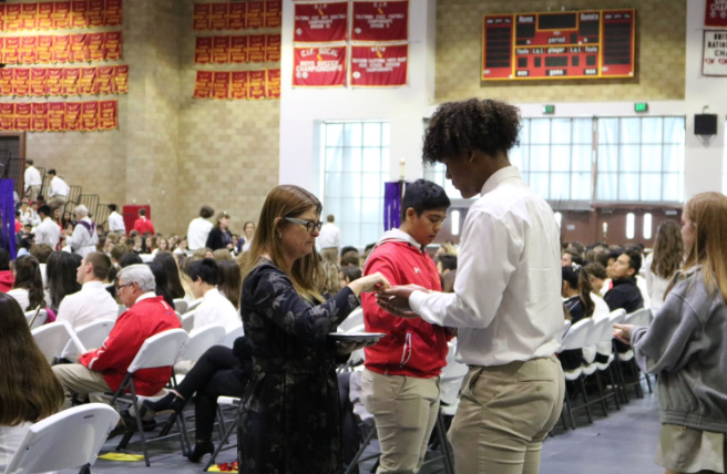 CCHS students receive the Eucharist at the Ash Wednesday liturgy, which was held in the Claver Center at Cathedral Catholic High School and led by Father Mike White.