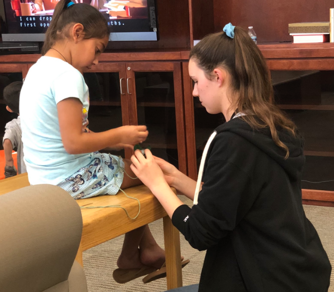 While on a service trip to the California School for the Deaf Riverside, Christine Walsh '20, a member of the American Sign Language Honor Society, teaches Laila, a young deaf girl, how to knit during a break on Saturday.