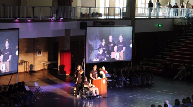 """Students Lauren Munro '19, Miles McCormick '19,  Caleb Price '19, and Jake Mitten '19 (left to right) speak at Tuesday's assembly, reflecting on their participation in the """"Every 15 Minutes"""" program."""