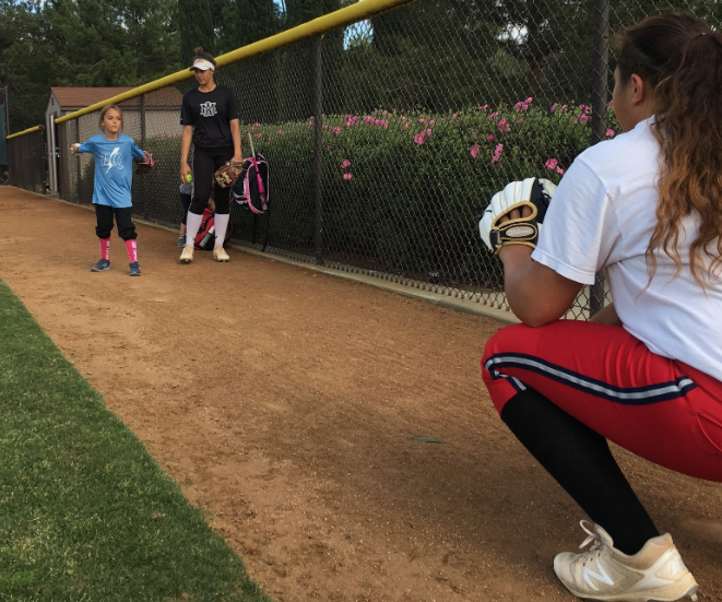 Varsity softball players Sara Rusconi '19 (middle) and Laurali Patane '20 (right) teach Dean of Counseling and Wellness Mrs. Ashley Bascom's daughter (left) how to pitch after practice Tuesday.